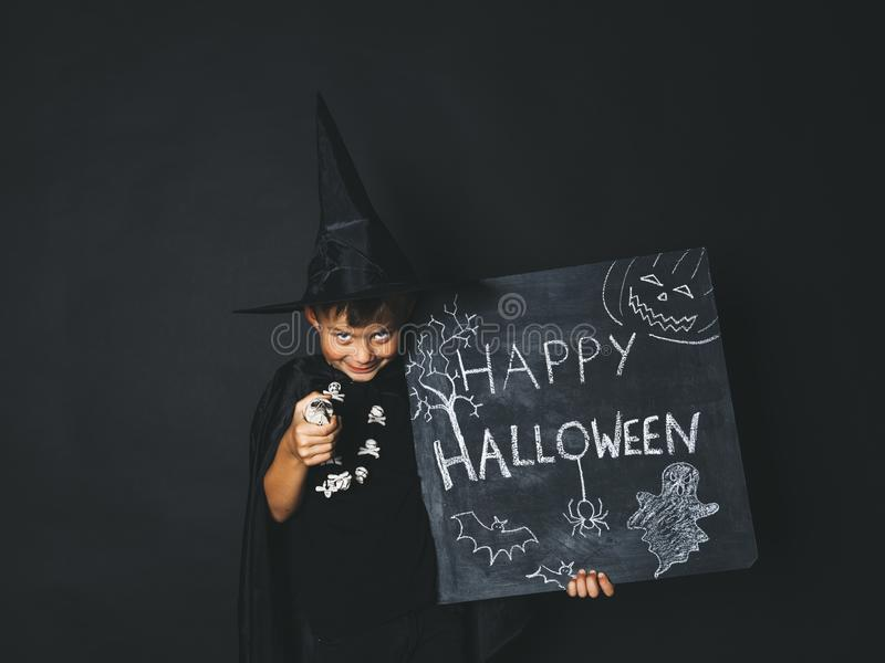 Young boy dressed as a magician is holding happy halloween chalkboard. In front of black background royalty free stock photography