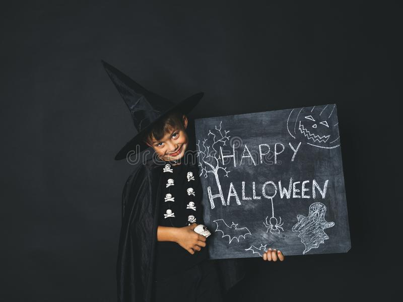 Young boy dressed as a magician is holding happy halloween chalkboard. In front of black background royalty free stock photos