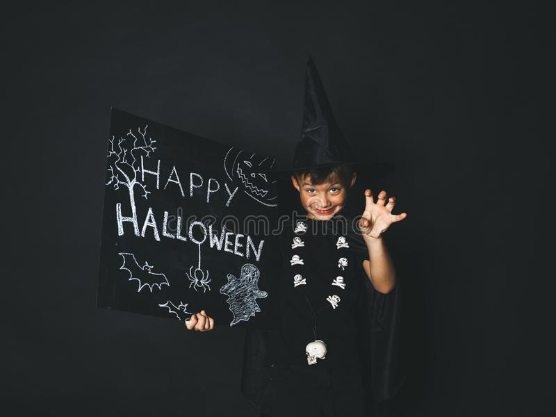 Young boy dressed as a magician is holding happy halloween chalkboard. In front of black background stock photo