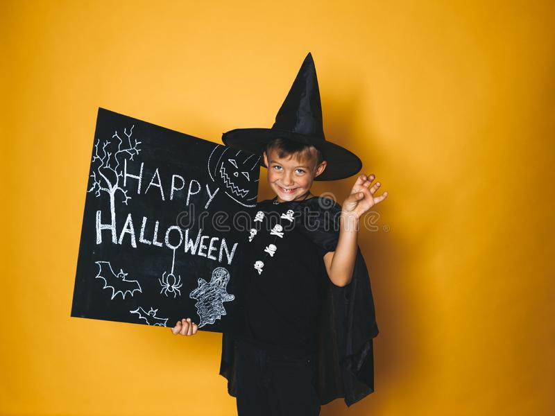 Young boy dressed as a magician is holding happy halloween chalkboard. In front of orange background royalty free stock photos