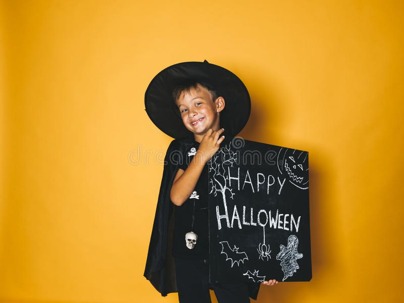 Young boy dressed as a magician is holding happy halloween chalkboard. In front of orange background royalty free stock photography
