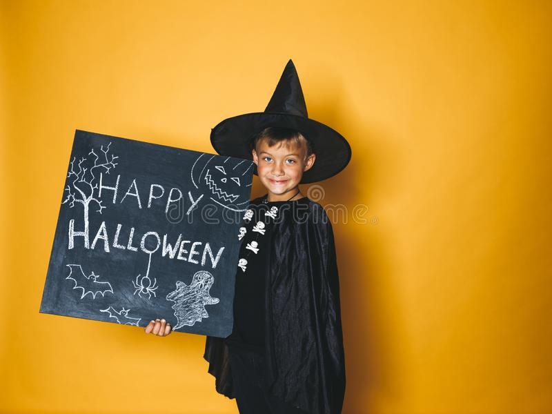 Young boy dressed as a magician is holding happy halloween chalkboard. In front of orange background stock photography