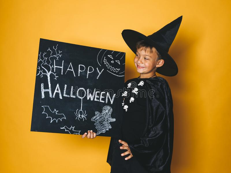 Young boy dressed as a magician is holding happy halloween chalkboard. In front of orange background royalty free stock photo