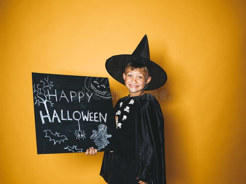 Young boy dressed as a magician is holding happy halloween chalkboard. In front of orange background stock images