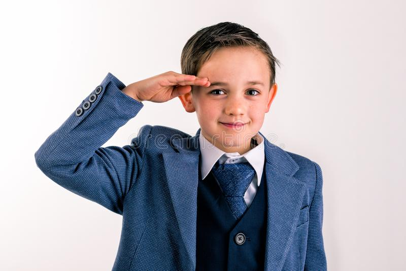 Young boy dressed up saluting stock photo