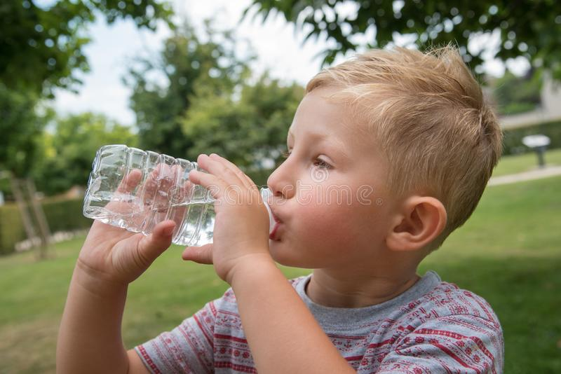 Young boy drinking water. Outdoor portrait stock photography