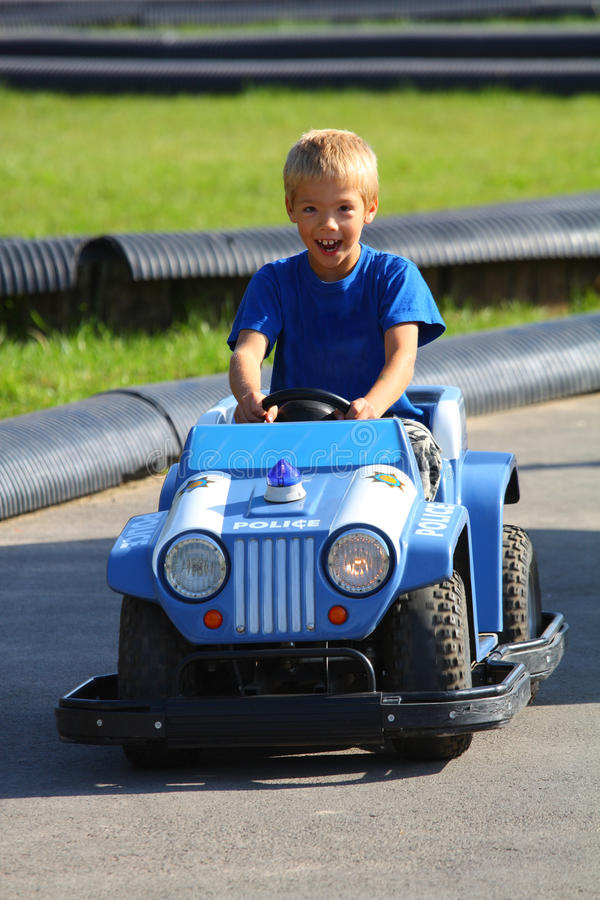 Young boy driving police car on street royalty free stock image