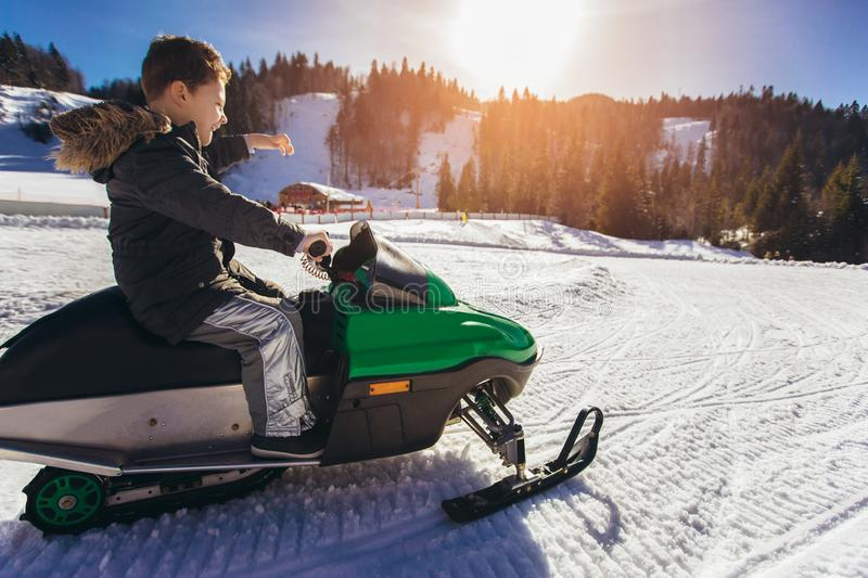 Boy driving snowmobile in a winter landscape royalty free stock image