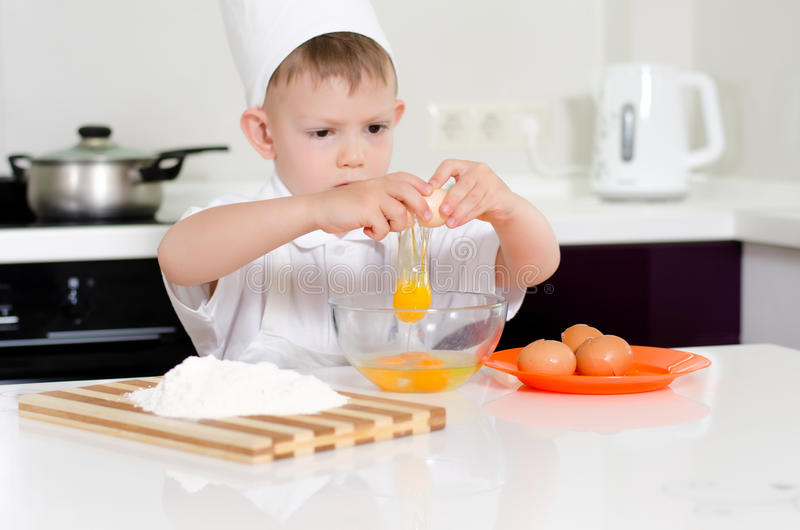 Young boy earning to be a chef. Young boy earning chef breaking eggs into mixing bowl look of concentration as he follows the recipe his chefs uniform royalty free stock photos