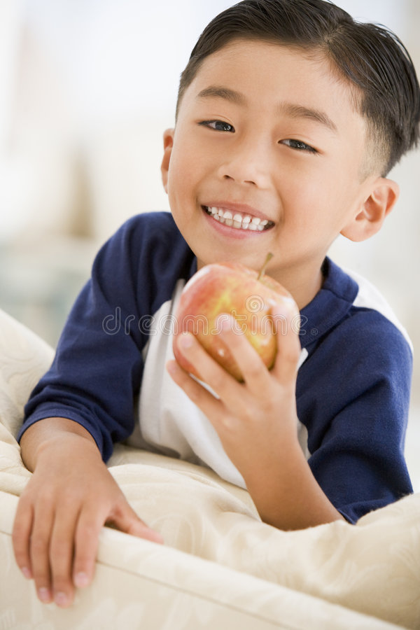 Download Young Boy Eating Apple In Living Room Stock Photo - Image: 5939036