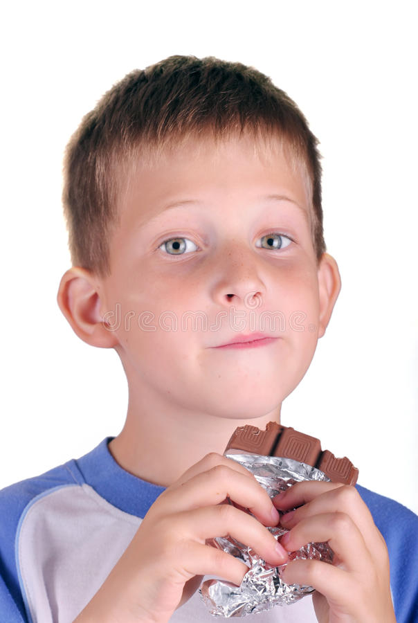 Young boy eating bar of chocolate stock photo