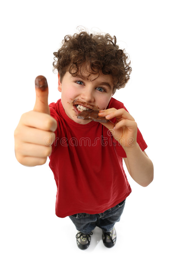 Young boy eating bar of chocolate. Showing OK sign isolated on white background royalty free stock image