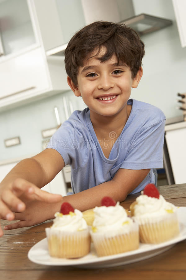 Young Boy Eating Cakes In Kitchen stock images