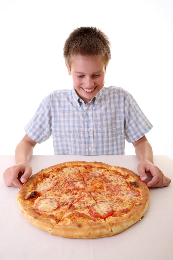 Young boy eating pizza stock photography