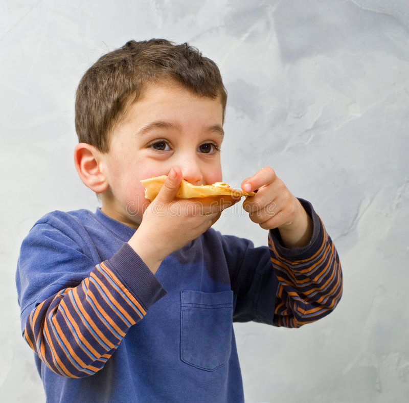 Young boy eating pizza stock image