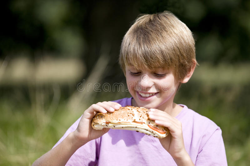 A young boy eating a sandwich royalty free stock photography