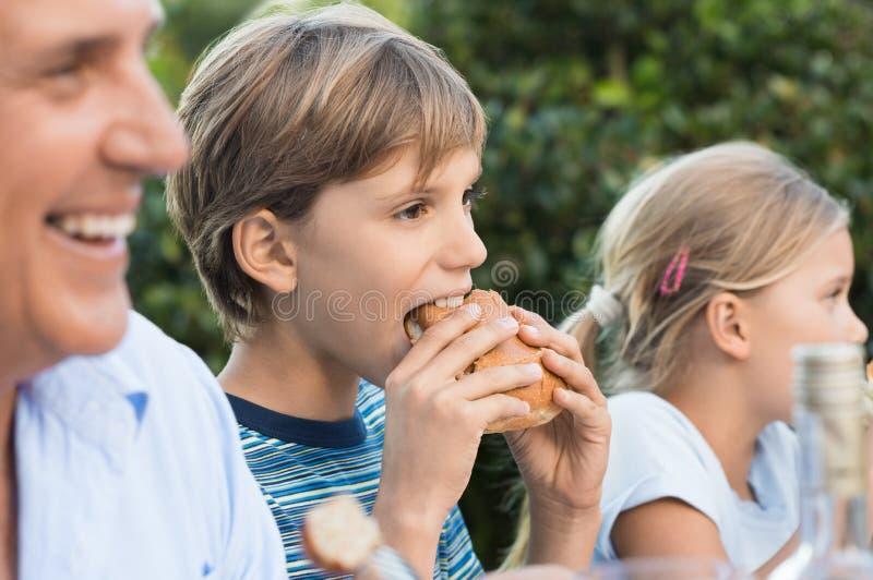 Young boy eating sandwich stock photos