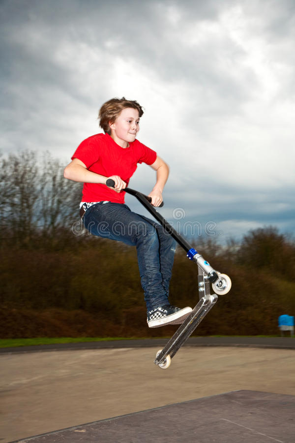 Young boy enjoys riding a scooter stock image