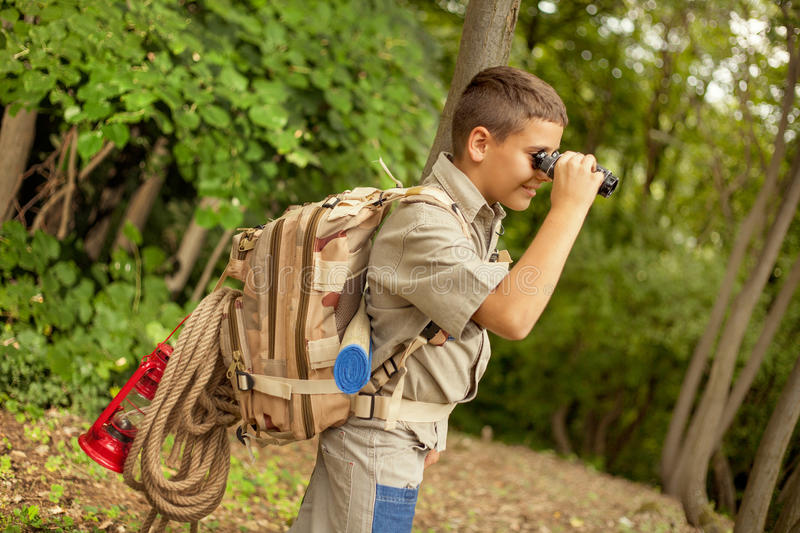 Young boy explores nature with binoculars on camping trip. Boys go hiking with backpacks on a forest road bright sunny day stock images