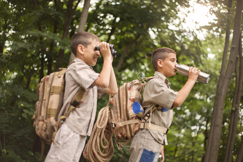 Young boy explores nature with binoculars on camping trip. Excited children on a camping trip in green forest stock image