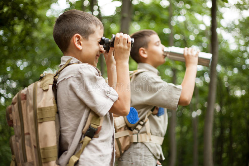 Young boy explores nature with binoculars on camping trip. Excited children on a camping trip in green forest stock images