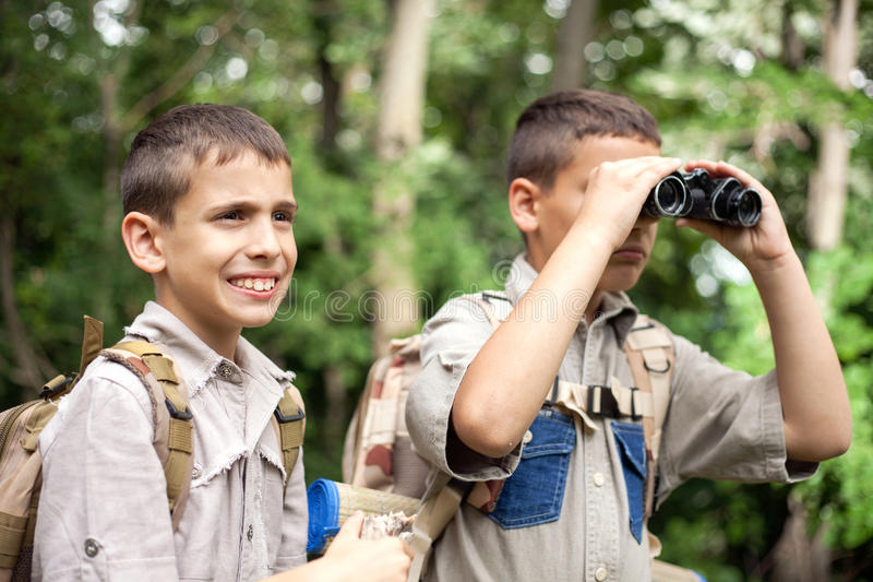 Young boy explores nature with binoculars on camping trip. Excited children on a camping trip in green forest royalty free stock photography