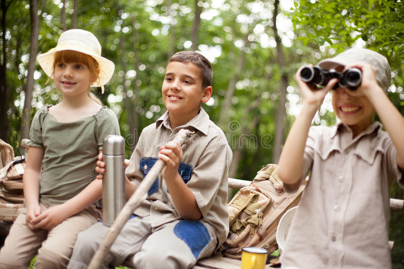 Young boy explores the nature with binoculars. Excited children on a camping trip royalty free stock photo