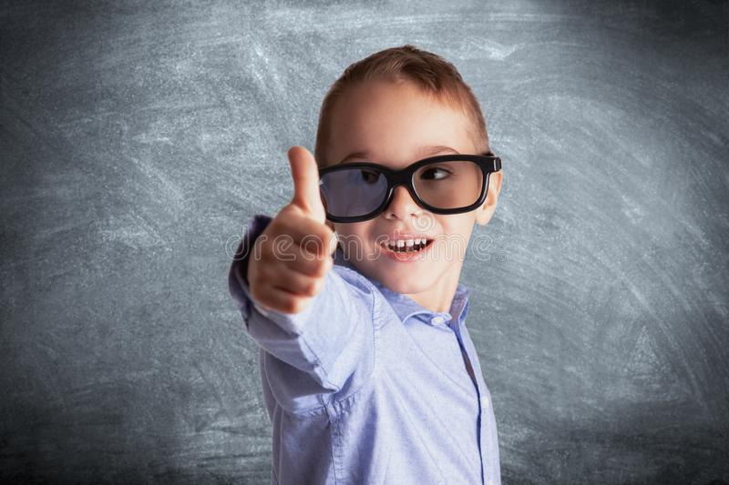 Young boy with eyeglasses in front of a school chalkboard showing thumbs up. Eye examination, education and learning concept.  stock photo