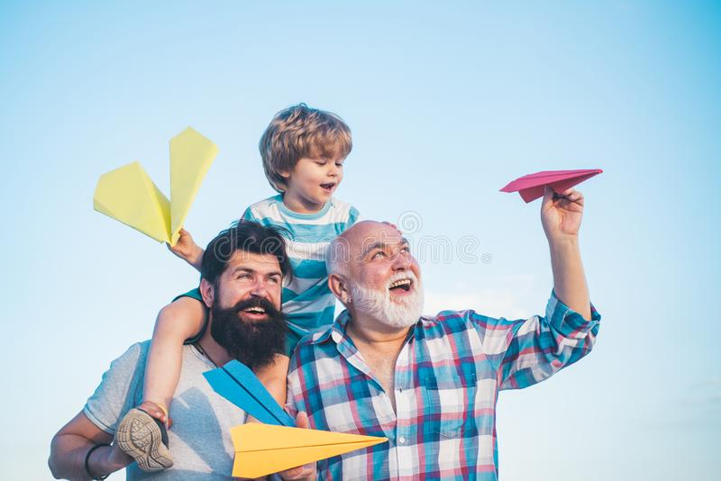 Young boy with father and grandfather enjoying together in park on blue sky background. Grandfather playtime. Happy stock photo