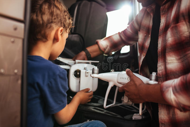 Young boy with father holding small drone on road trip stock images