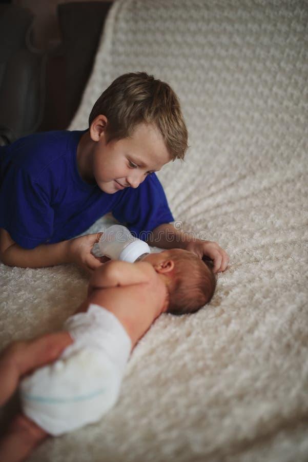 Boy feeding newborn baby with bottle of milk. Young boy feeding newborn baby with bottle of milk royalty free stock photo