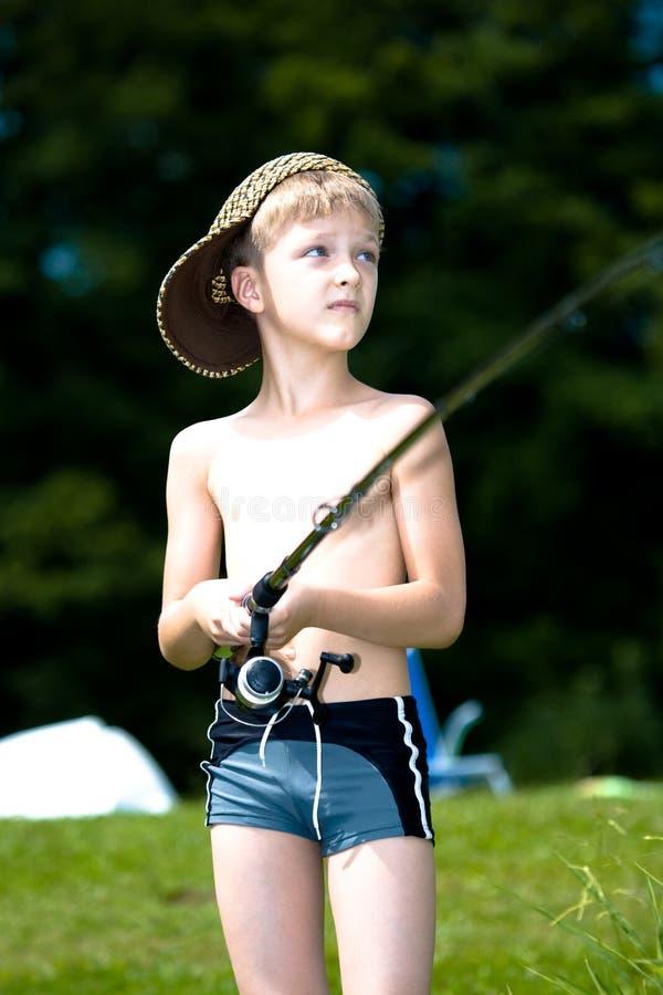 Young boy fishing at a lake royalty free stock image