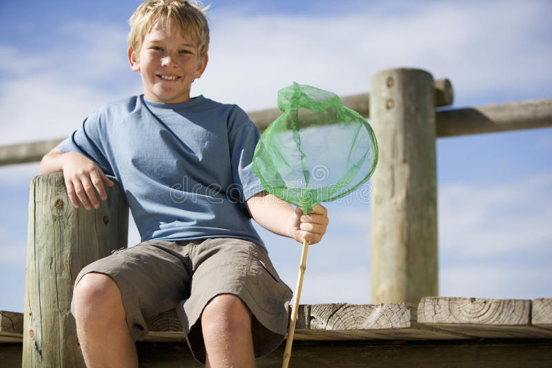 A young boy with a fishing net stock images