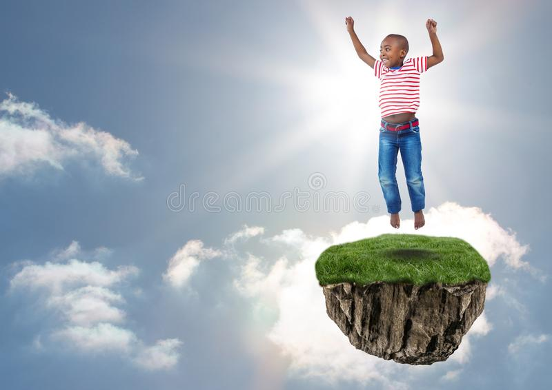 Young boy on floating rock platform in sky jumping stock image