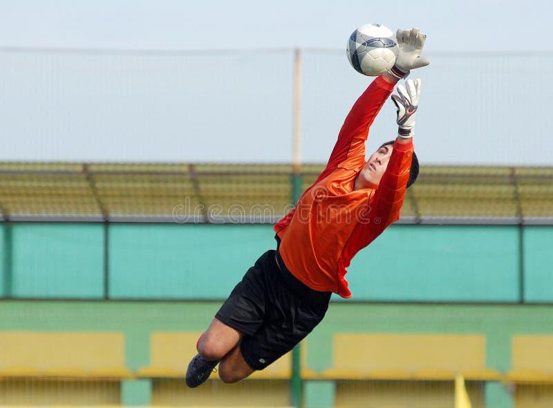 Young boy football or soccer goalkeeper jump parade royalty free stock photography