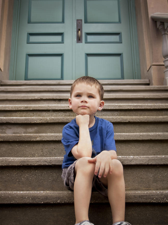 Young boy on the front steps of his school. A low-angle view of a young boy sitting on the front steps of his school and thinking and contemplating. Serious stock image