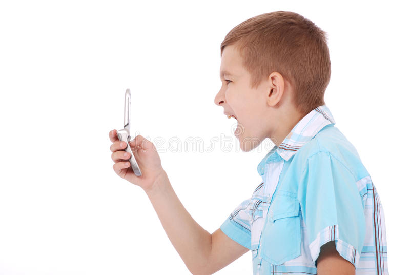 A young boy is furiously screaming. Into his cell phone royalty free stock photo