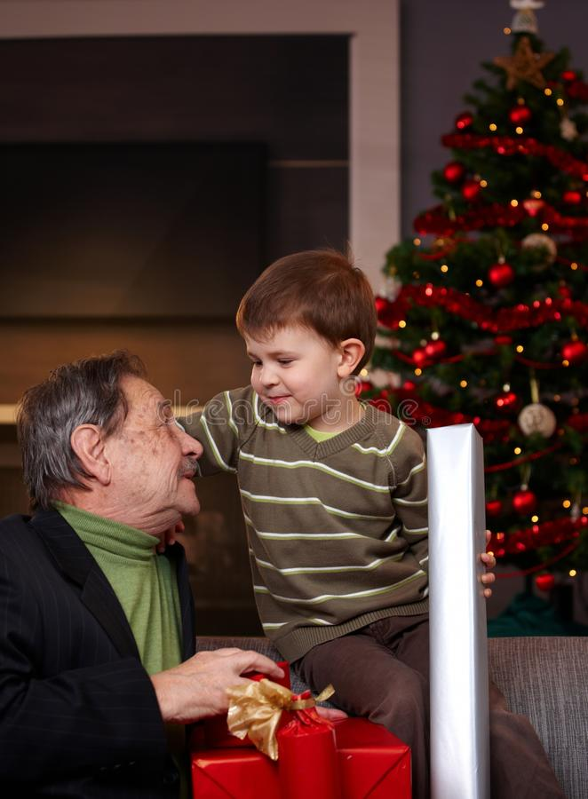 Young boy getting christmas present from grandfather. Small boy getting christmas present from happy grandfather, looking each other, smiling stock photography