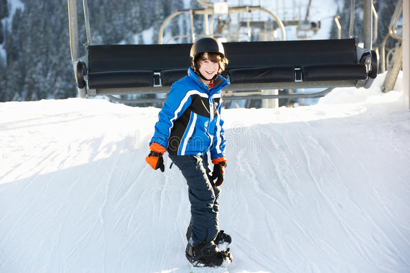 Young Boy Getting Off Chair Lift On Ski Holiday. In Mountains Smiling At Camera royalty free stock photography