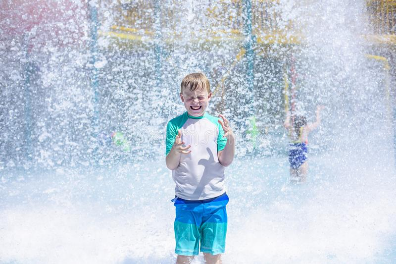 Young boy getting soaking wet while at an outdoor water park. Lots of water splashing water behind the boy. He is closing his eyes anticipating getting wet and royalty free stock photos