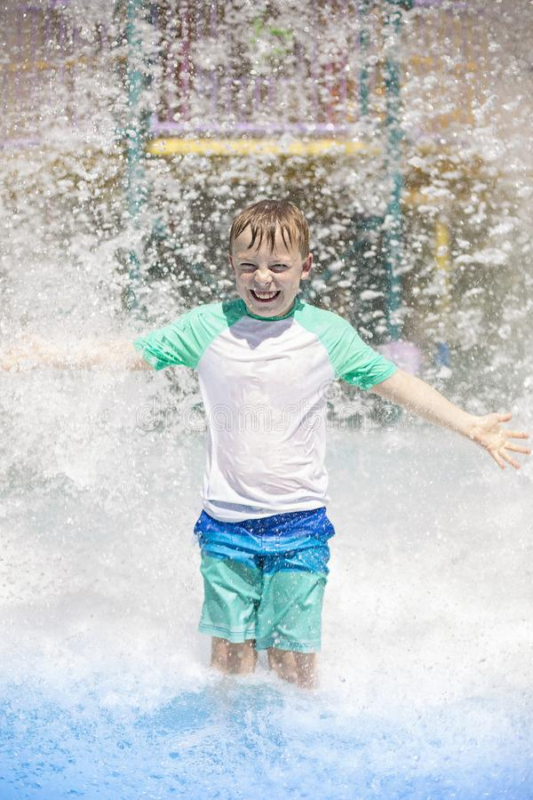 Young boy getting soaking wet while at an outdoor water park. Lots of water splashing water behind the boy. He is smiling and anticipating getting wet and stock image