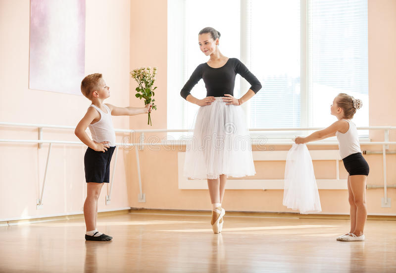 Young boy and girl giving flowers and veil to older student while she is dancing en pointe stock image