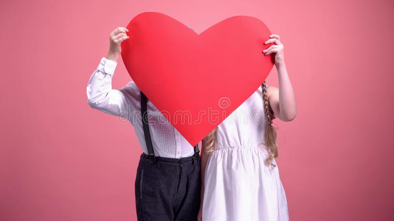 Young boy and girl hiding behind red paper hearts and kissing, Valentines day royalty free stock image