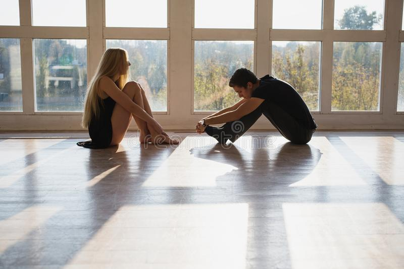 Difficult situation in life. Conceptual photography. A young boy and girl with long blond hair standing in front of the window. Dancers during a workout royalty free stock images