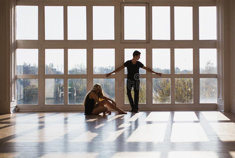 Difficult situation in life. Conceptual photography. A young boy and girl with long blond hair standing in front of the window. Dancers during a workout royalty free stock photos
