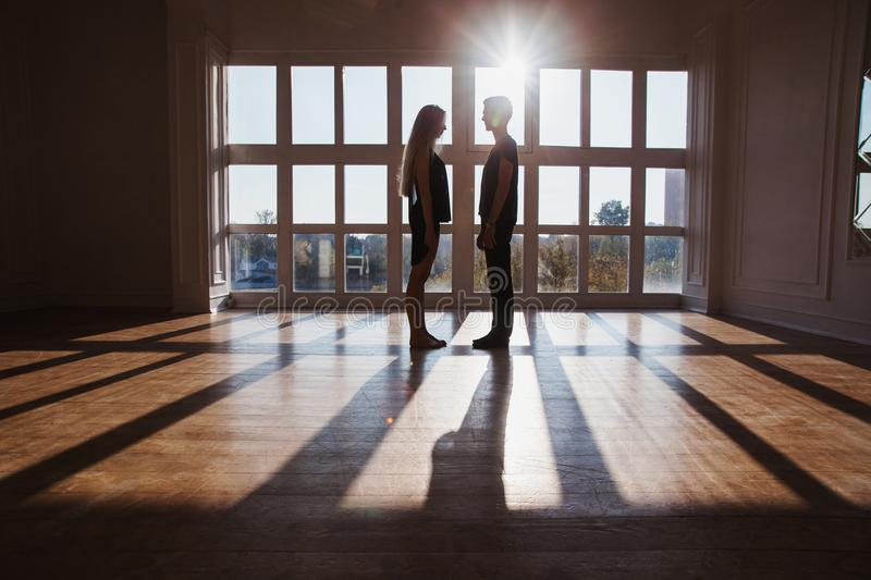 The difficult situation in life. Conceptual photography. A young boy and girl with long blond hair standing in front of the window. Dancers during a workout royalty free stock photography