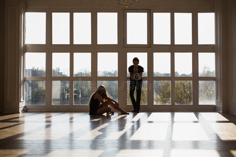 A young boy and girl with long blond hair standing in front of the window. Dancers during a workout. Problems and difficulties in relations. The difficult stock photo