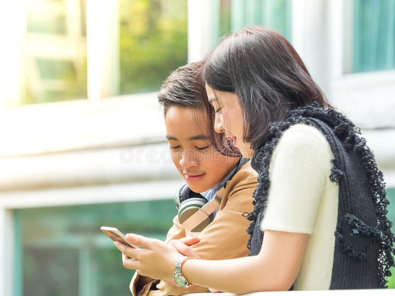 Young boy and girl play games on mobile phones royalty free stock photography