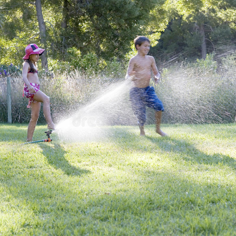 Young boy and girl playing with water in the garden royalty free stock image