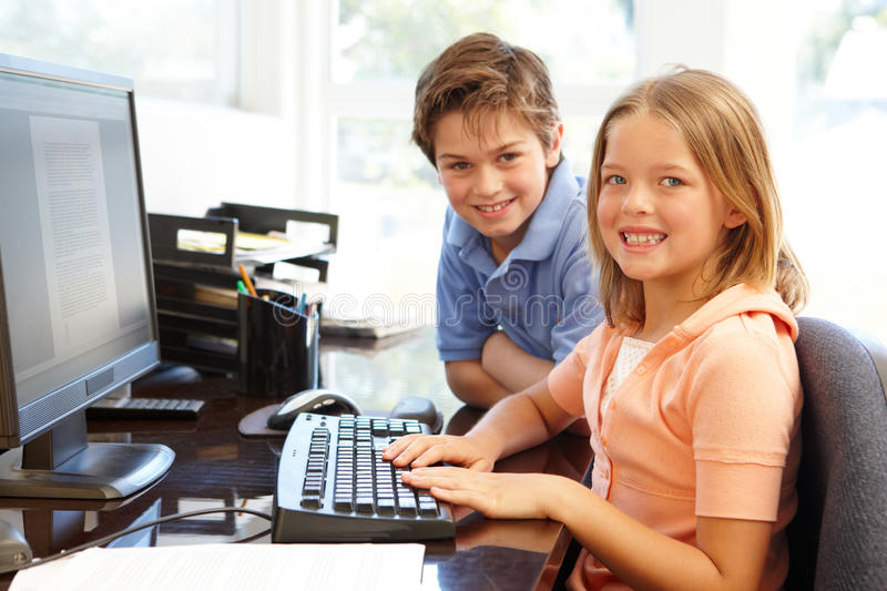 Young boy and girl using computer at home royalty free stock photos